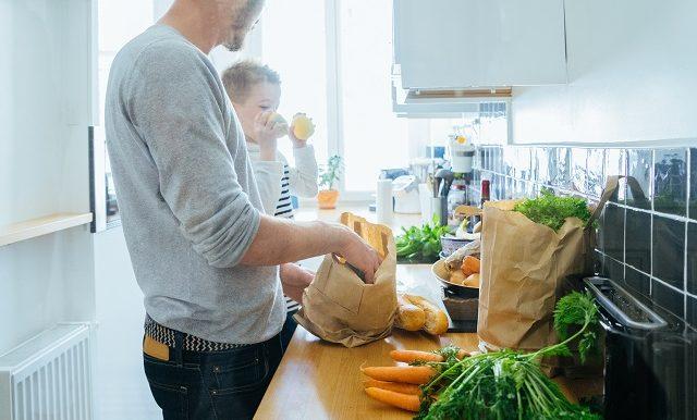 Un père et son fils vident des sacs d'épicerie dans la cuisine