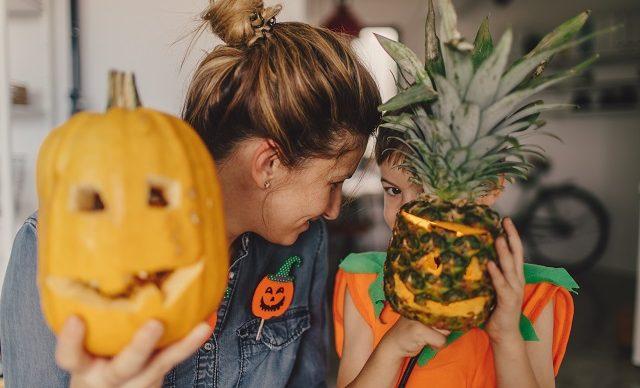 une mère et son fils montrent leur citrouille et ananas décorés pour l'halloween