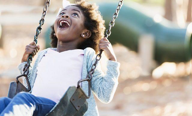 une petite fille à la peau noire se balance en riant