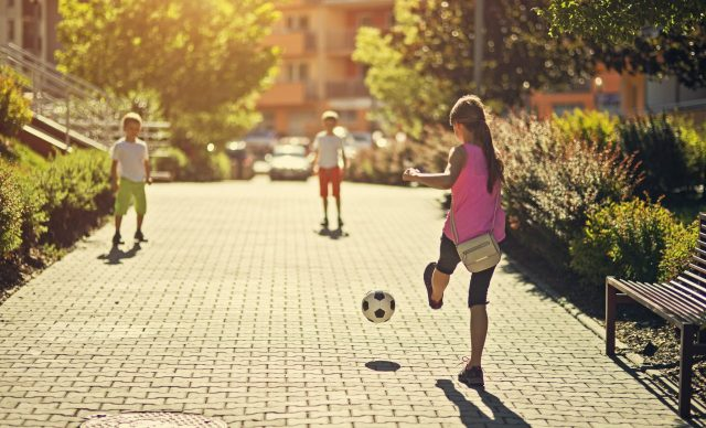 trois enfants jouent au soccer dans la ruelle