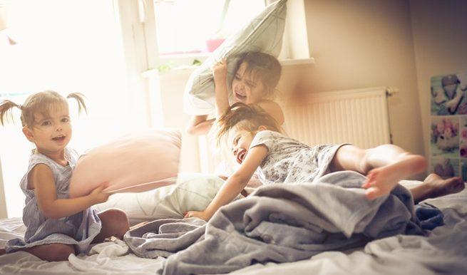 3 enfants qui font une bataille d'oreillers dans un lit