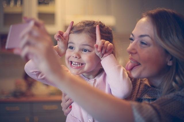Une petite fille fait une grimace en prenant un selfie avec sa mère