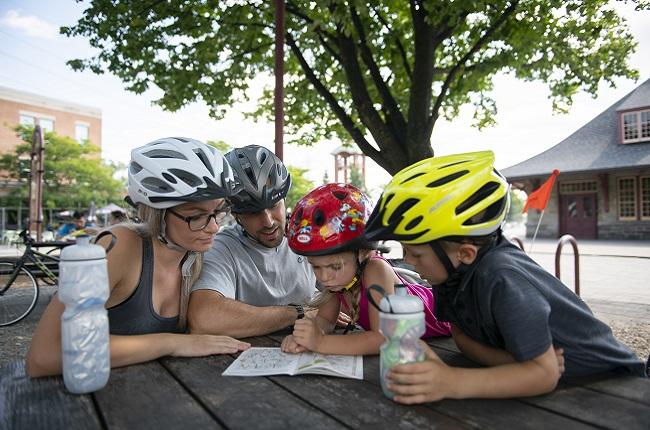 une famille portant des casques de vélos regardent une carte