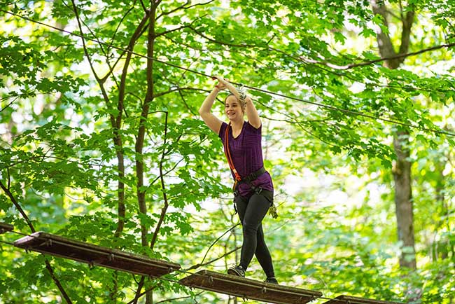 femme sur un parcours hébertisme entre les arbres