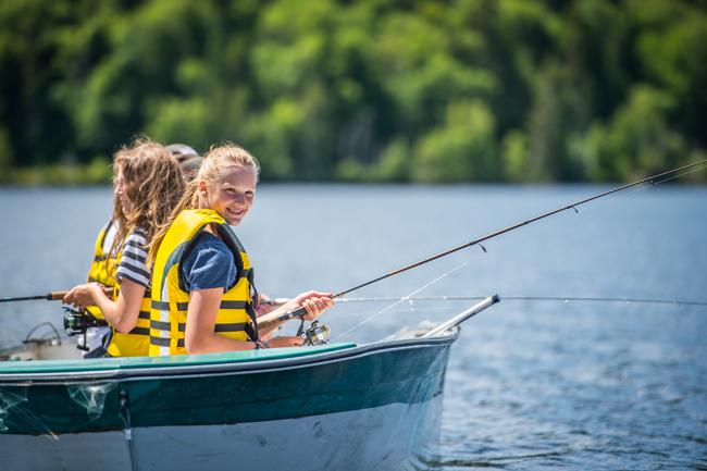 enfants qui pêchent dansune chaloupe avec gilets de sauvetage