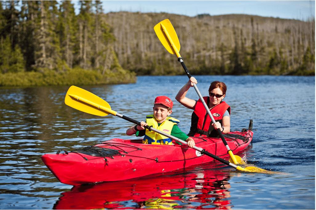 Un garçon et une femme qui pagaient dans un kayak rouge