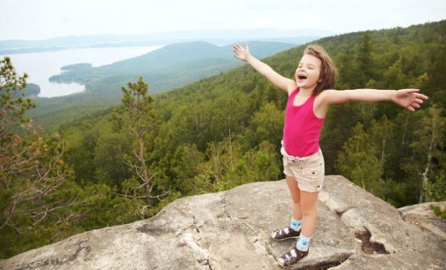 fillette au sommet d'une montagne