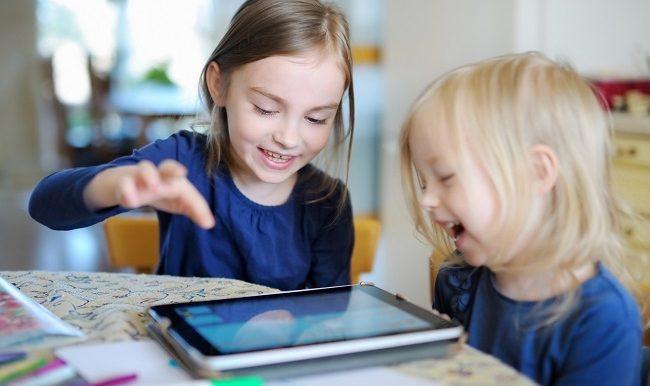 deux enfants devant une tablette électronique