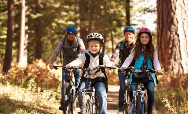 garçon qui fait du vélo de montage avec sa soeur et ses parents