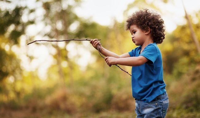enfant qui joue avec des bâtons